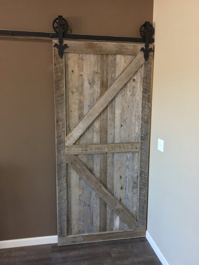 Closer view of the gray reclaimed wood sliding door.