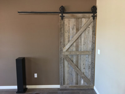 This view shows the gray reclaimed wood sliding door and track. The door features a double z pattern.