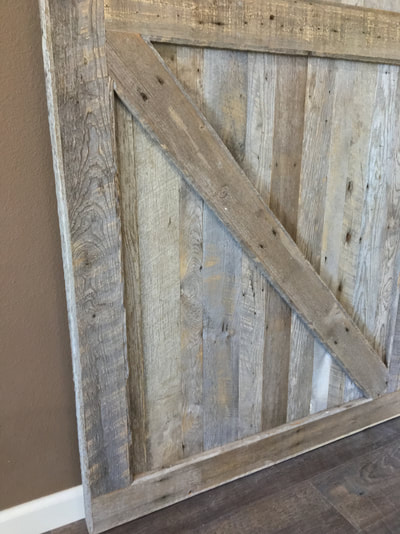 Close up view of the gray  reclaimed wood sliding door. This picture shows a close up of the bottom diagnol piece that makes up the double z pattern.