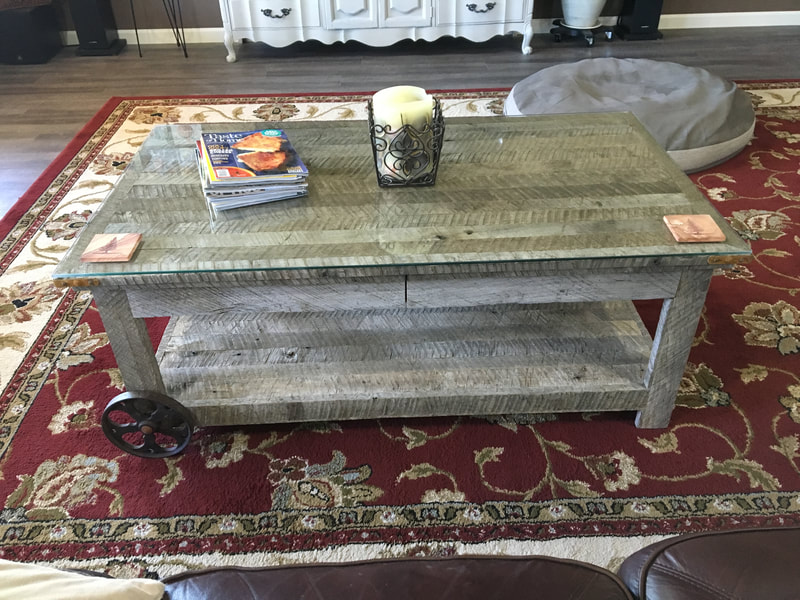 Front view of the antique wheel and gray reclaimed coffee table.