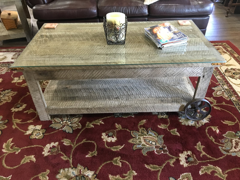 Backside view of the antique wheel and gray reclaimed wood coffee table.
